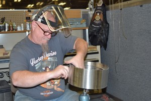 Jon Cannaday, an employee at Fortville Feeders, sands the edges of a feeder bowl part. Even small metal spurs can cause problems in the finished product.