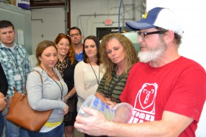 Tony Vivaldi, brewmaster at Wooden Bear Brewing, cracks open a container of hops, a key ingredient in brewing beer. Class members (from left) Rachel Cremeans, Lisa Thompson, Matt Davis, Summer Grinstead and Debbie Grass take a closer look.